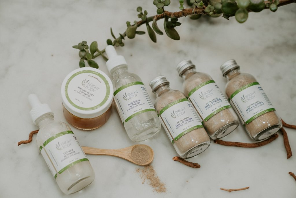 Bright Body products in a row with greenery