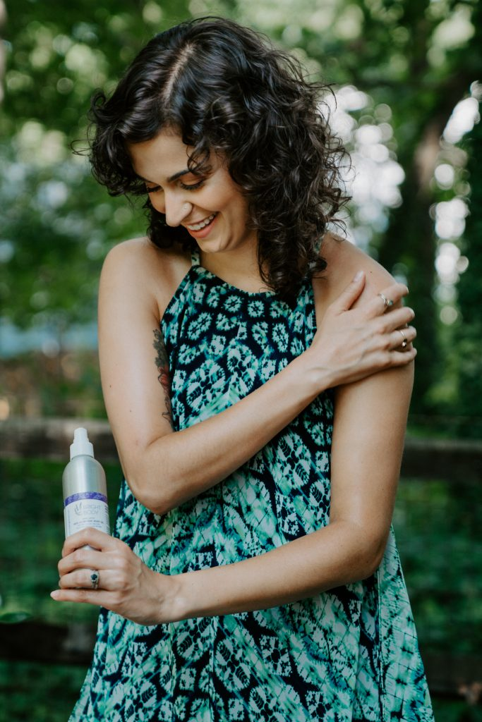 Bright Body Founder Gabi Day in green dress in woods holding product
