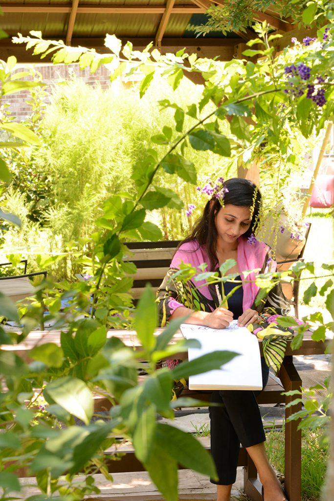 Loveleen, founder of Designs by Loveleen, making art on drawing pad