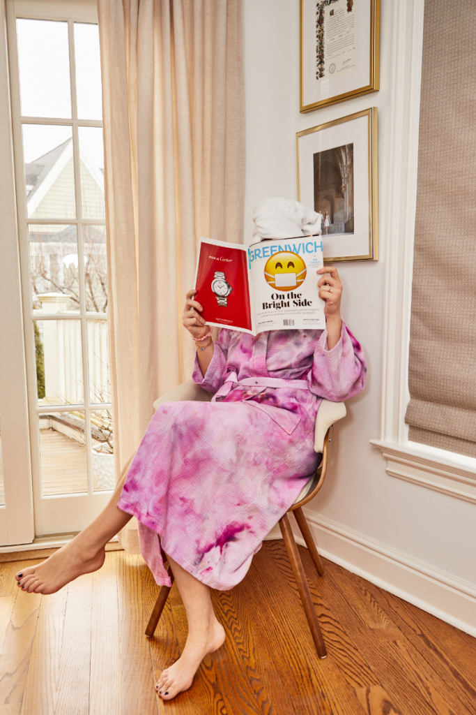 Girl with towel in hair reading magazine with smilie face in pink tie dye robe