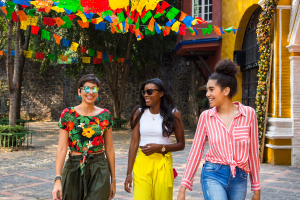 Three women walking in Mexico wearing colorful clothing with a colorful backdrop