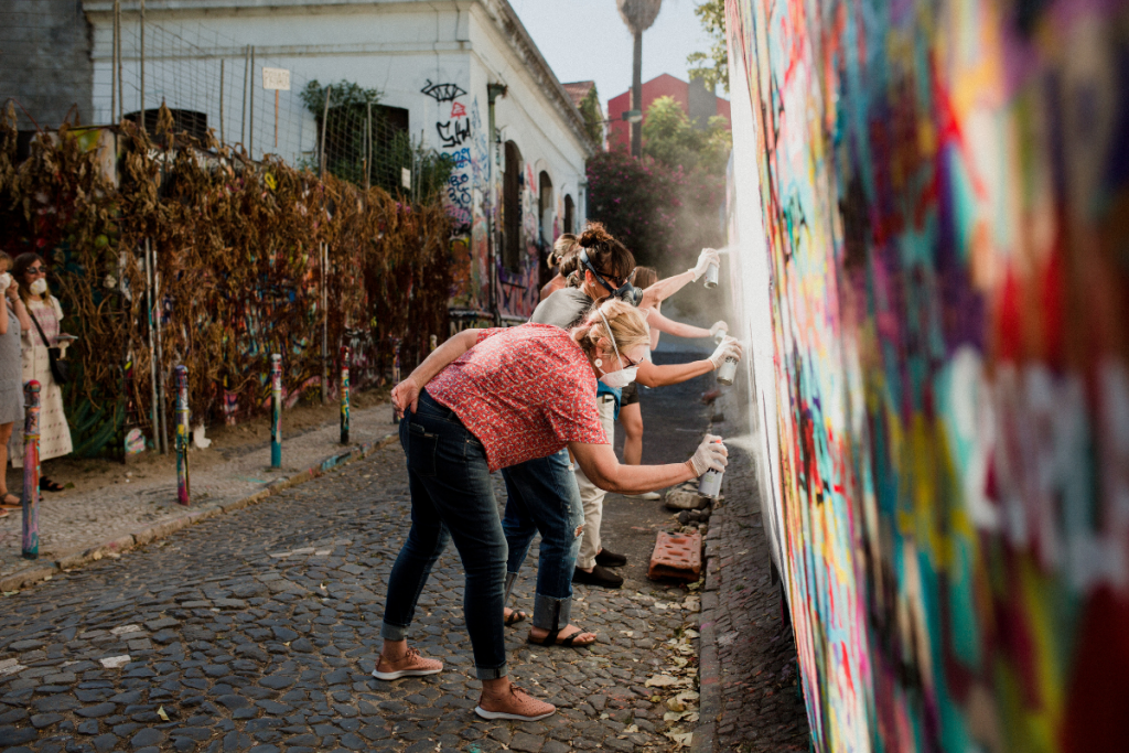 Women learning how to graffiti a wall in Portugal