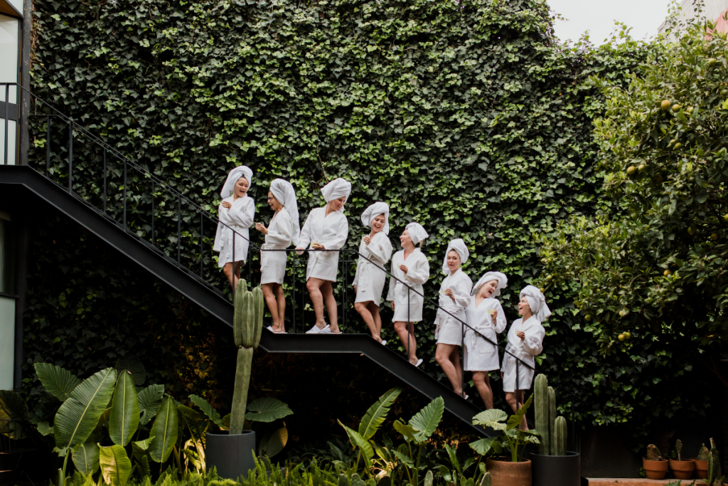 Women wearing white robes and white towels on their heads lined up on staircase