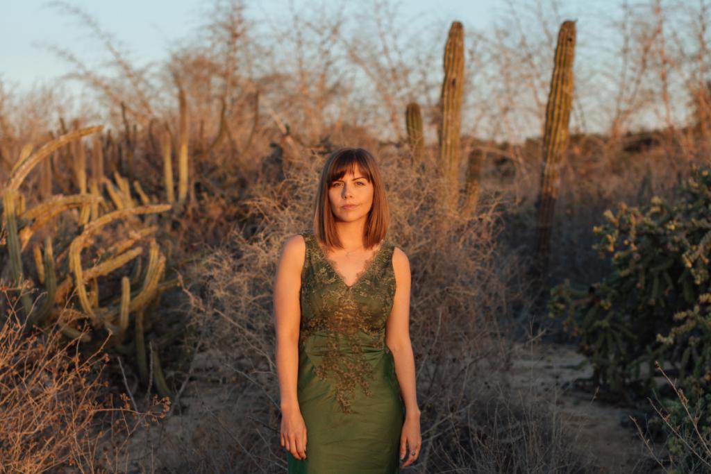 Wild Terrains founder Lauren Bates in Olive green dress in front of cacti