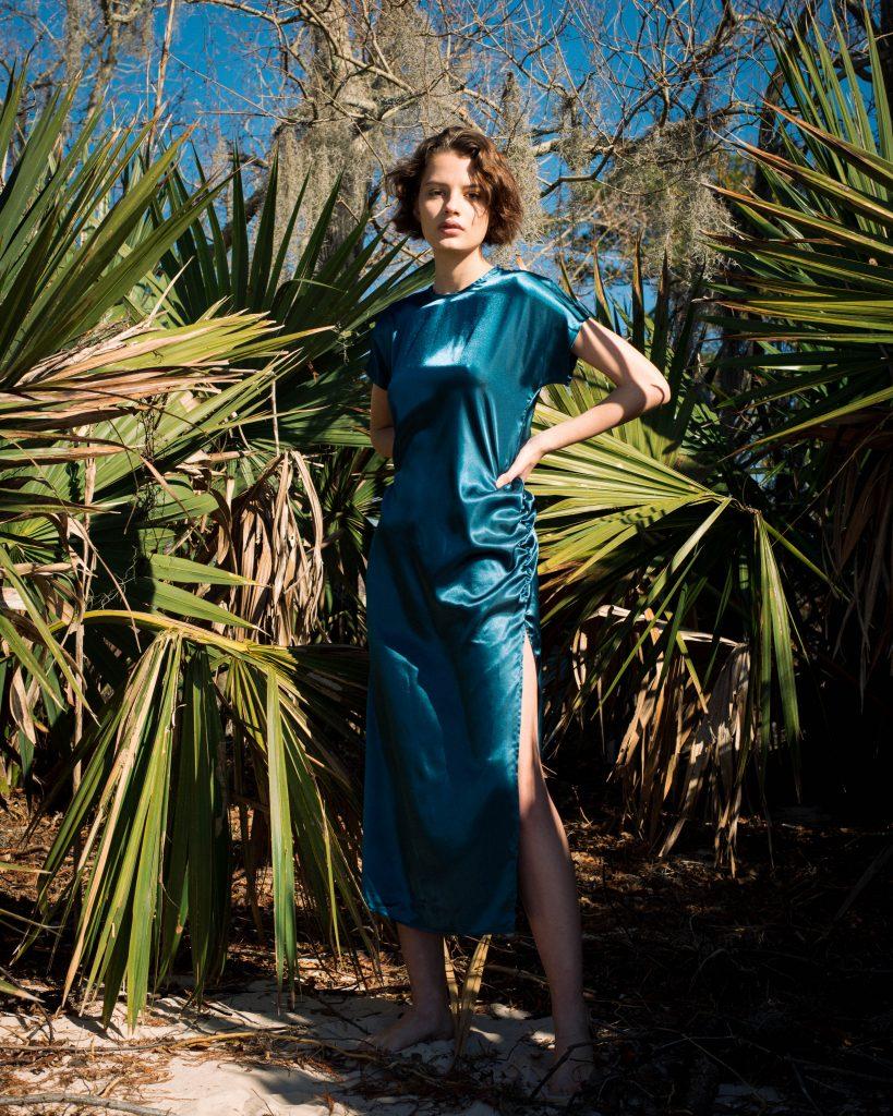 Woman standing near green palms in silky green/blue Noyette dress