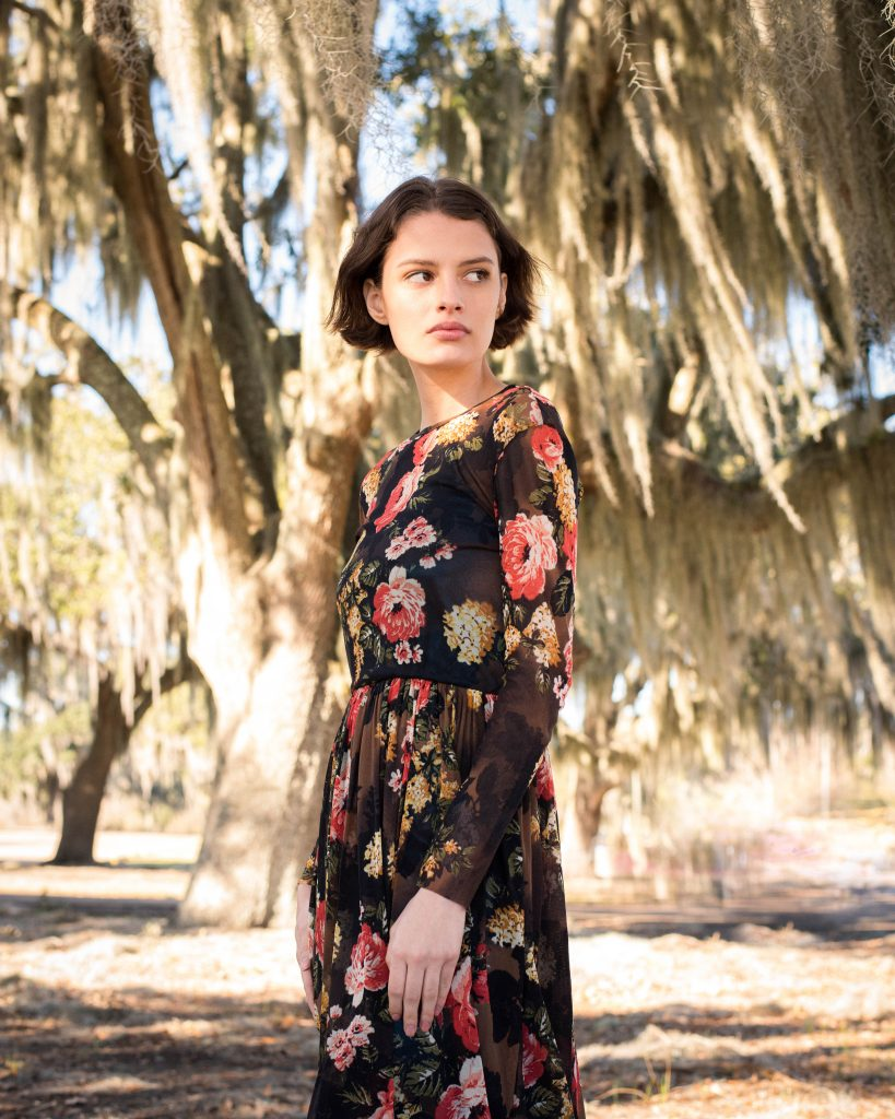 Girl standing amongst palm trees in dark dress with pink florals by Noyette