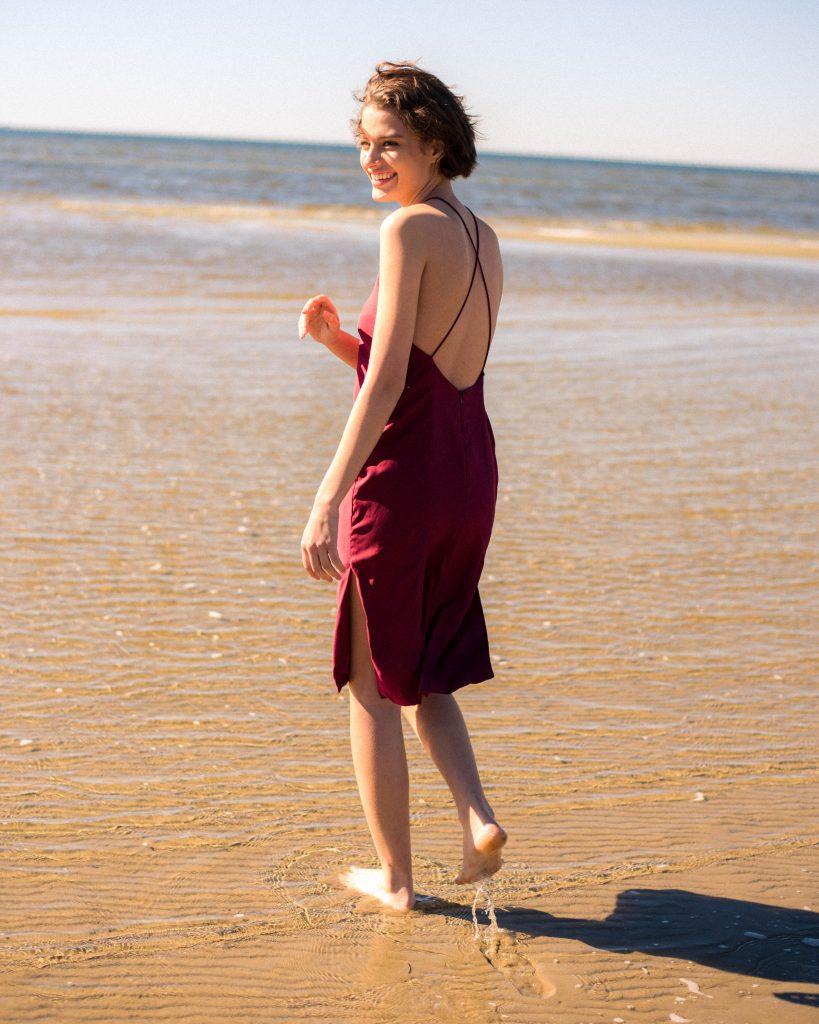Woman standing in water on beach in deep wine red dress by Noyette