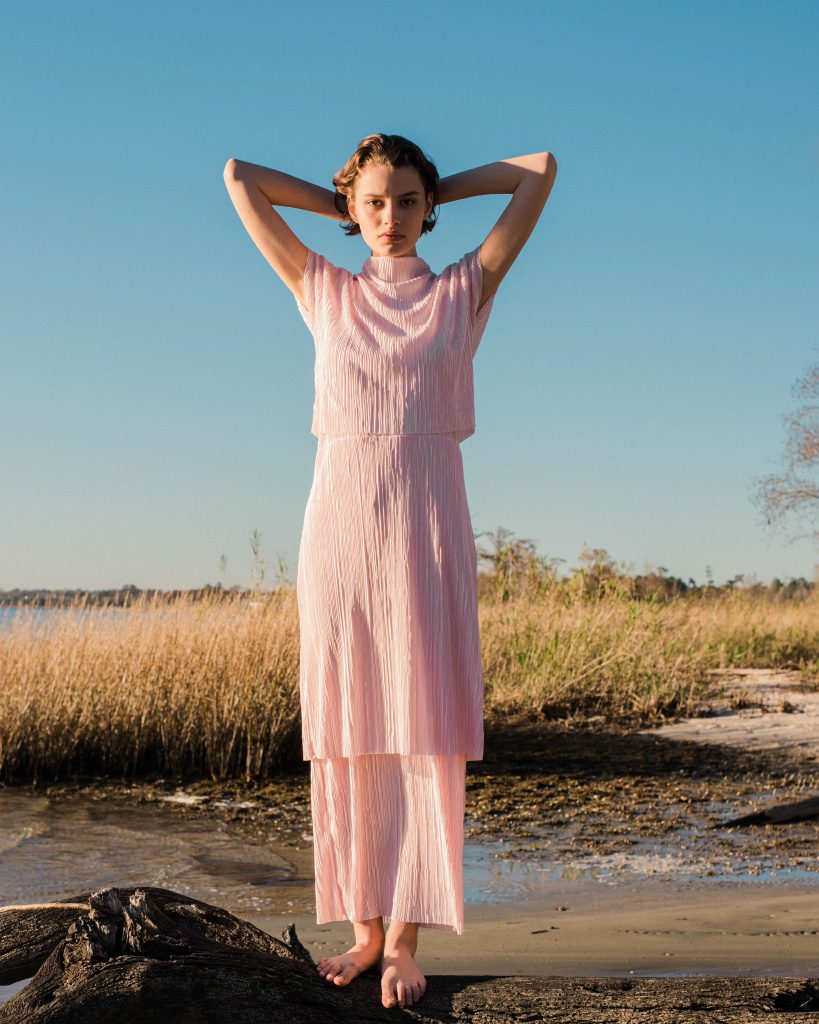 Woman standing on marshy beach in light pink layered dress by Noyette