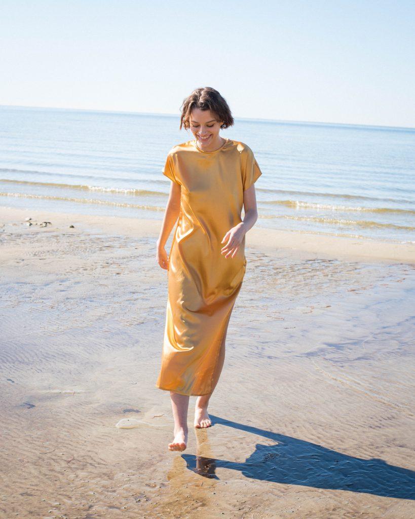 Woman smiling, walking on beach in yellow short-sleeved dress by Noyette